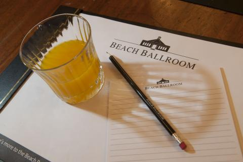 Glass of juice and a pencil on a Beach Ballroom headed notepad